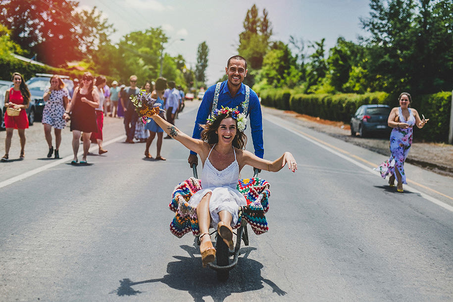 bride is taken in a wheelbarrow for the groom after the wedding ceremony