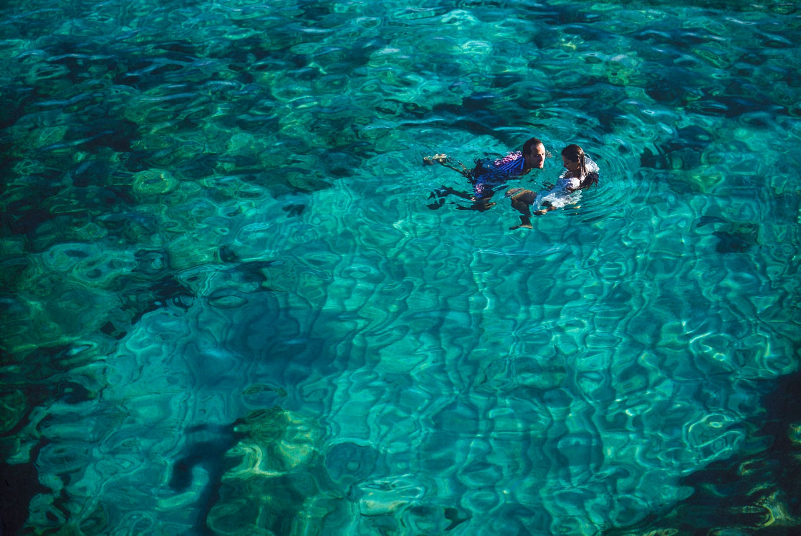 bride and groom swimming in a mallorca cala