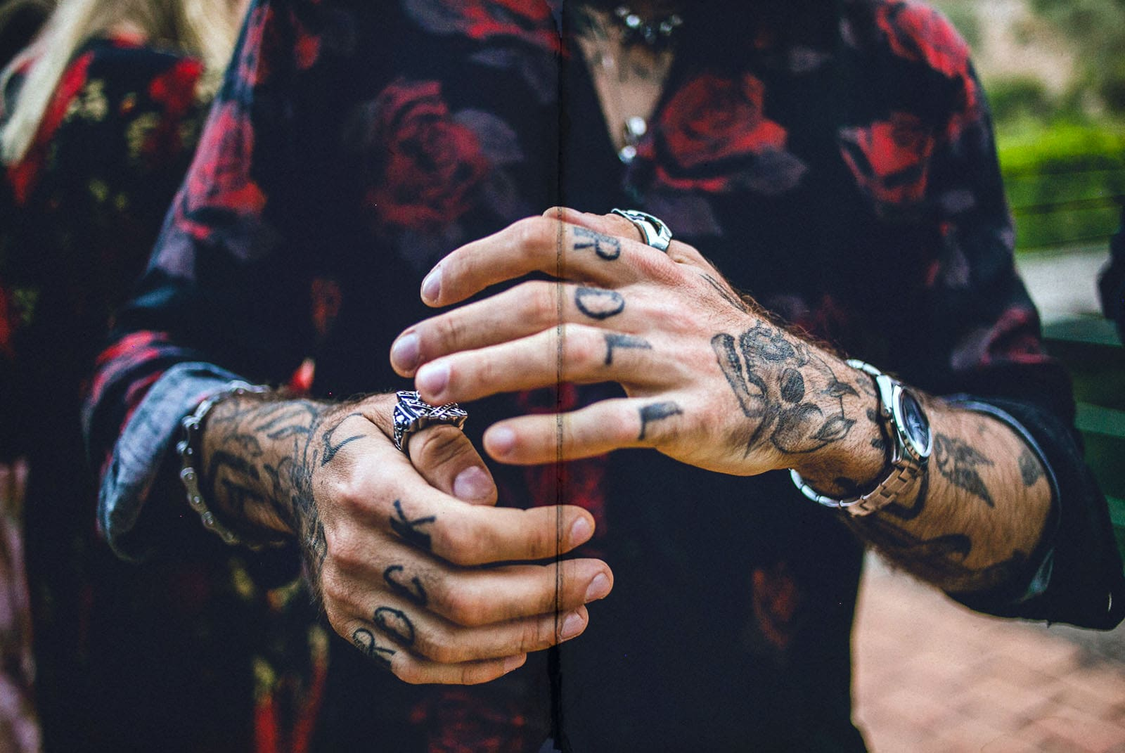 hands with tattoos of rock and roll