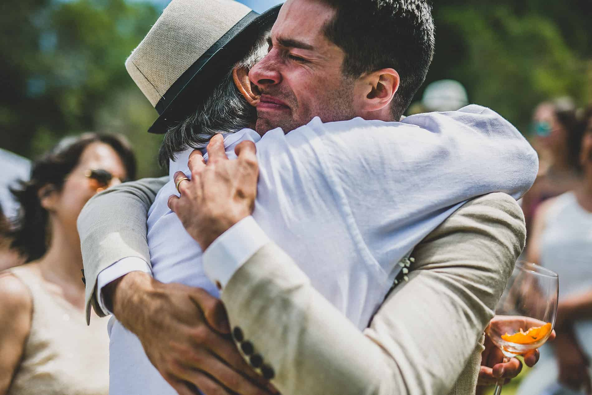 groom hugging his father crying