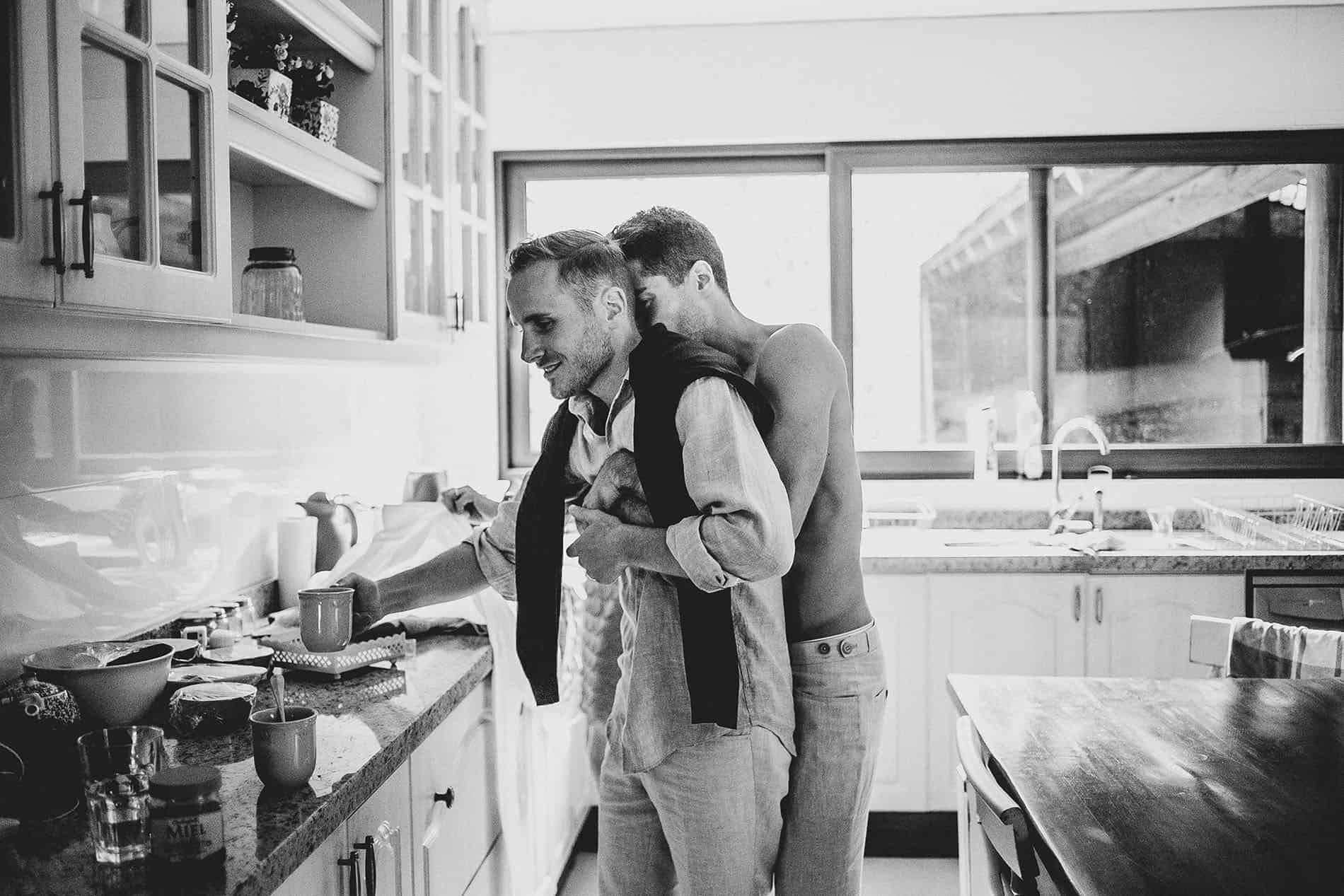 grooms hug each other in the kitchen
