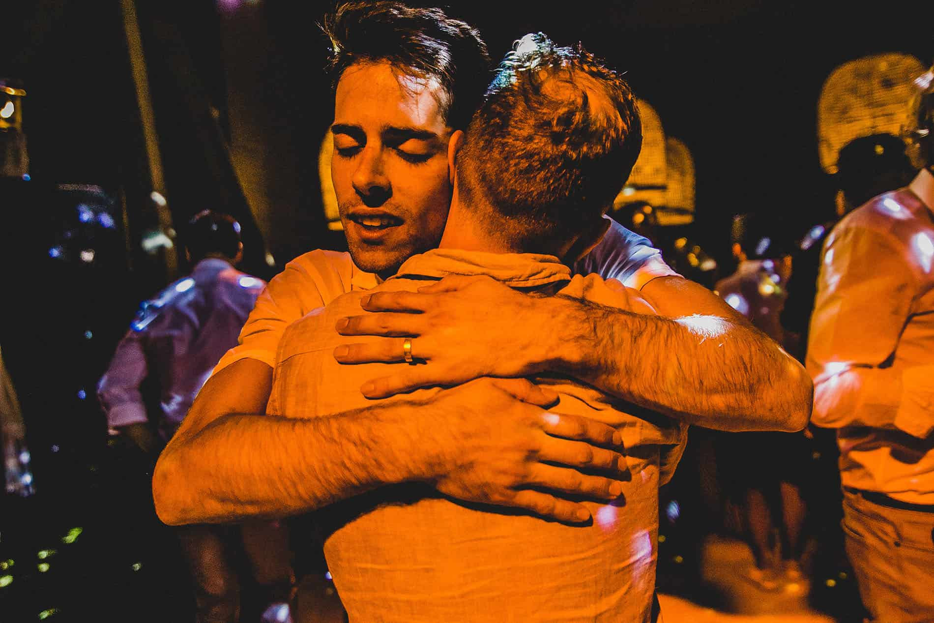 grooms hug each other with an orange light