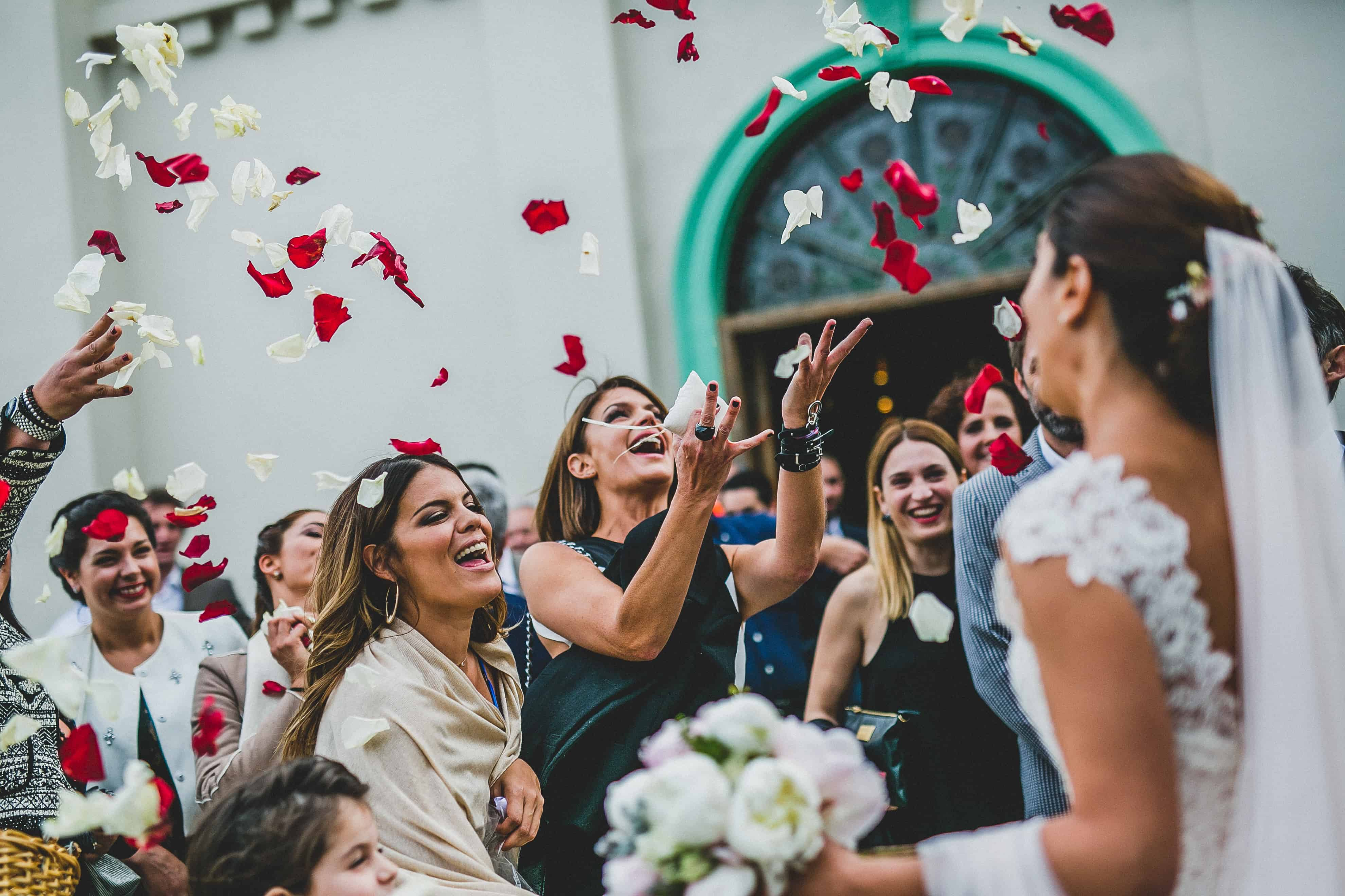 people throwing flowers to the bride