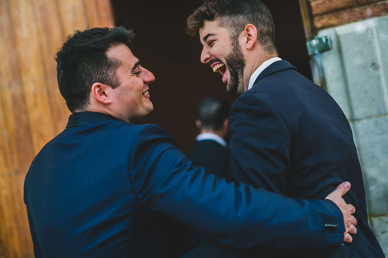 groom laughing saying hi to his friends