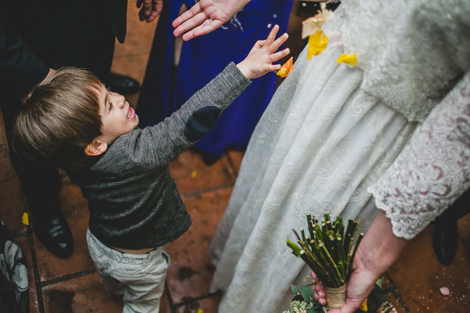 little kid throws petals to the bride