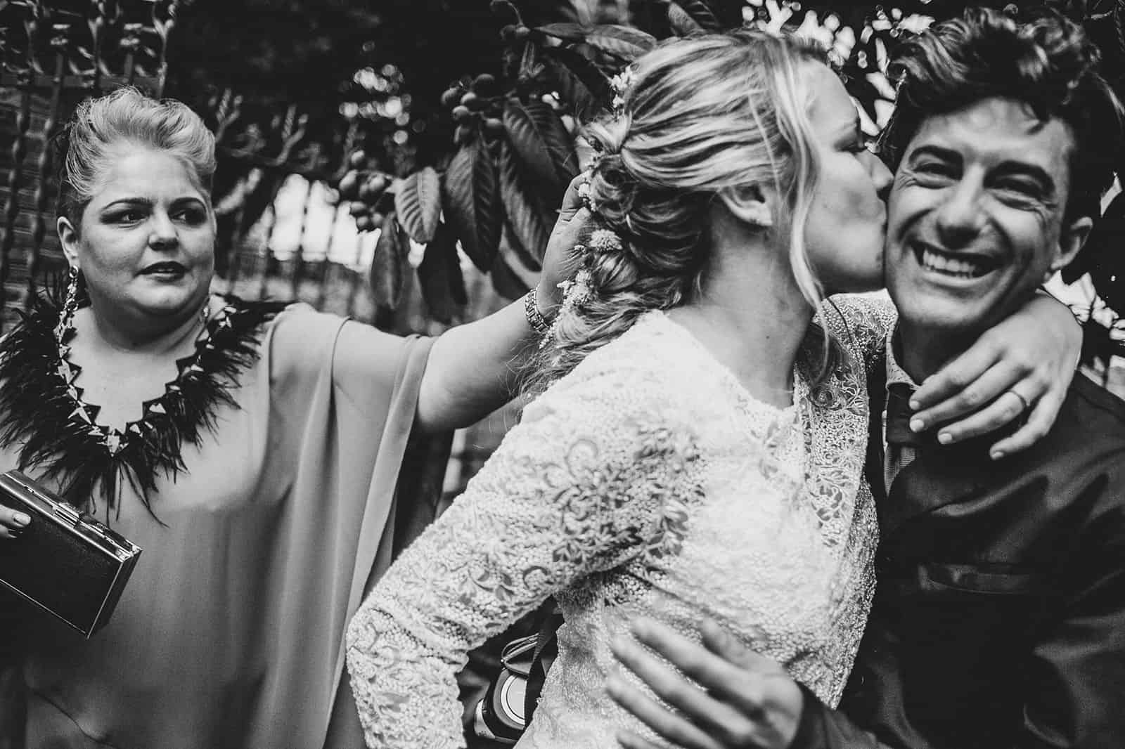 bride kiss a friend while a woman laughs
