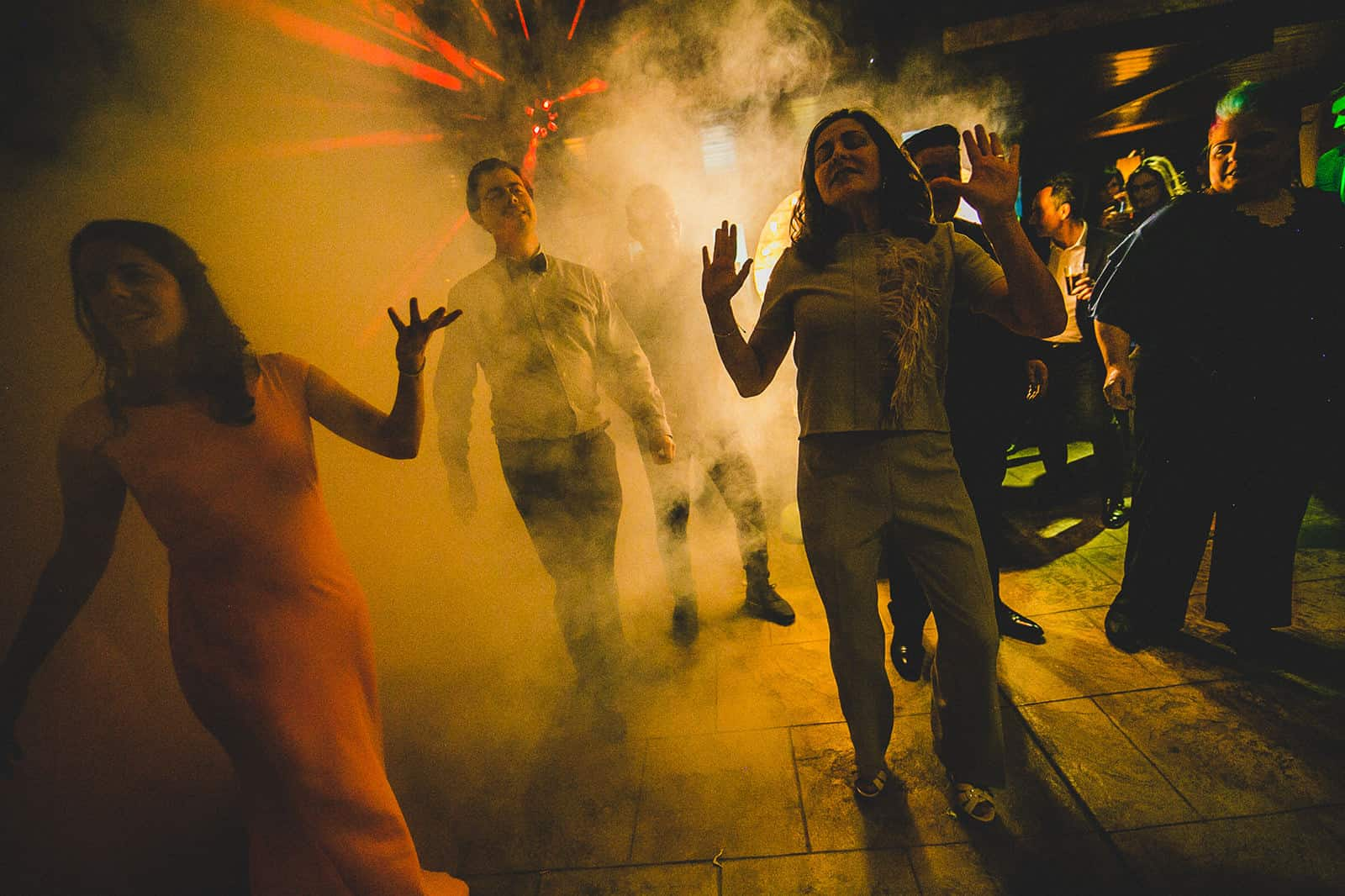 people dancing in the middle of the smoke bomb