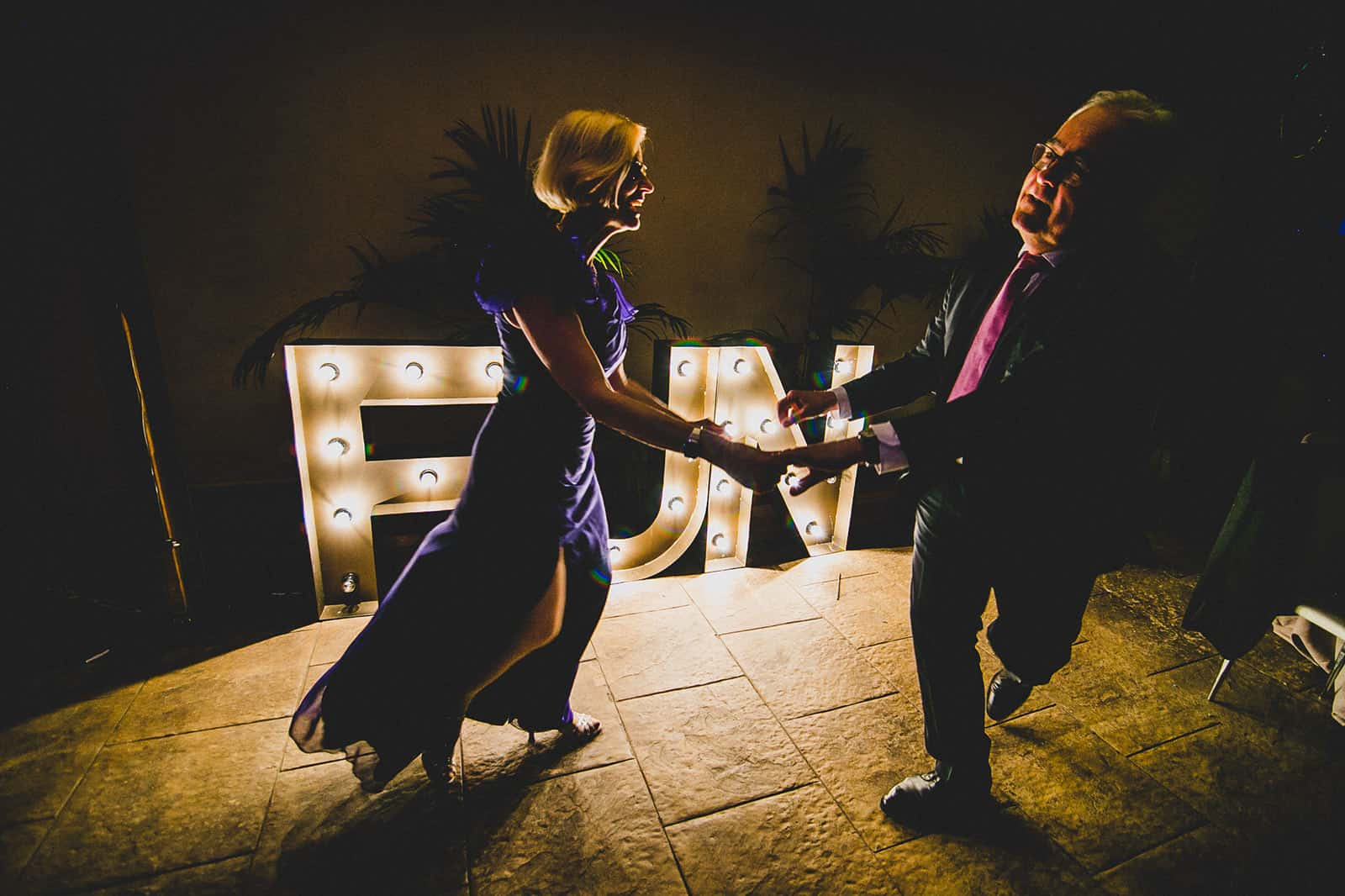 couple dancing in front of the Fun sign
