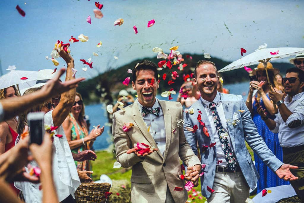 groom and groom going out of the ceremony surrounded by flower petals