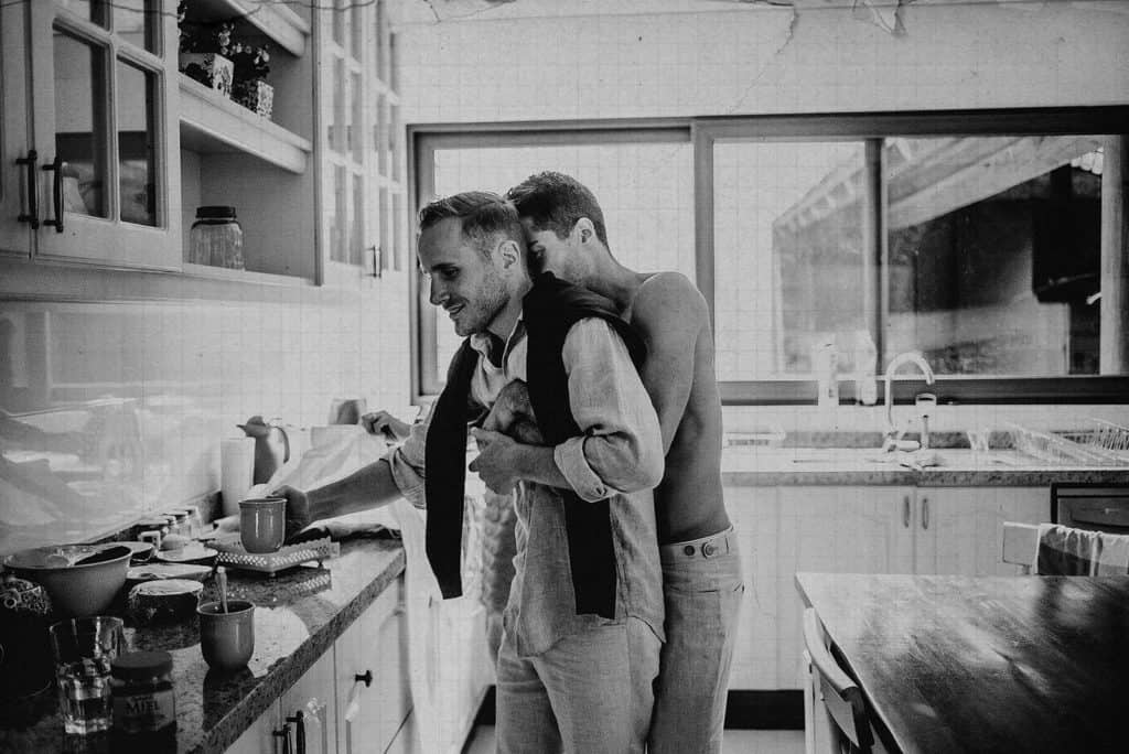 same sex couple hugging in the kitchen