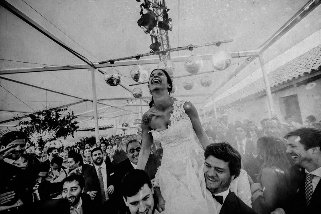 Bride is raised in her arms by her friends