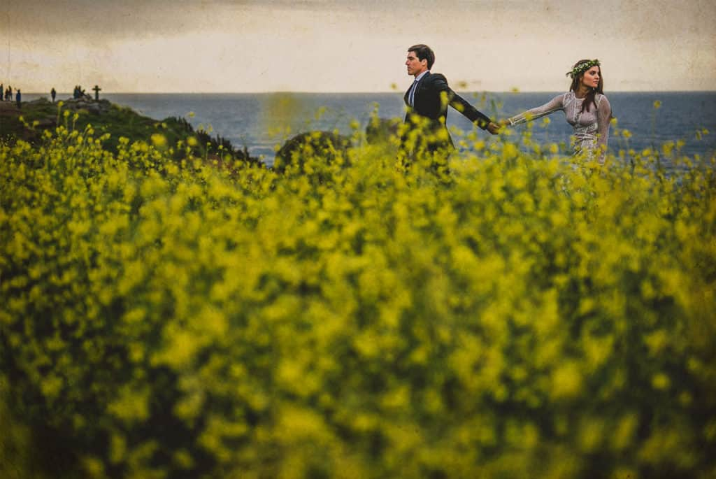 bride and groom walking in a yellow flowers field