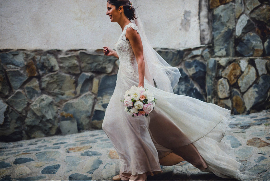 bride walking with her dress against the wind