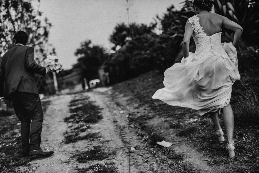 bride and groom walking in a hill against the wind