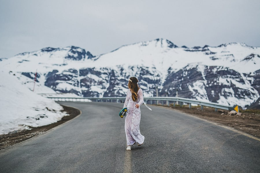 alternative bride with a skate walking down in a high mountain road