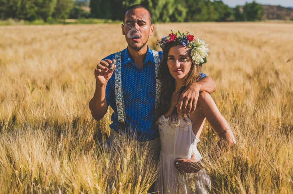 alternative bride and groom smoking a cigar in the summer wheat field