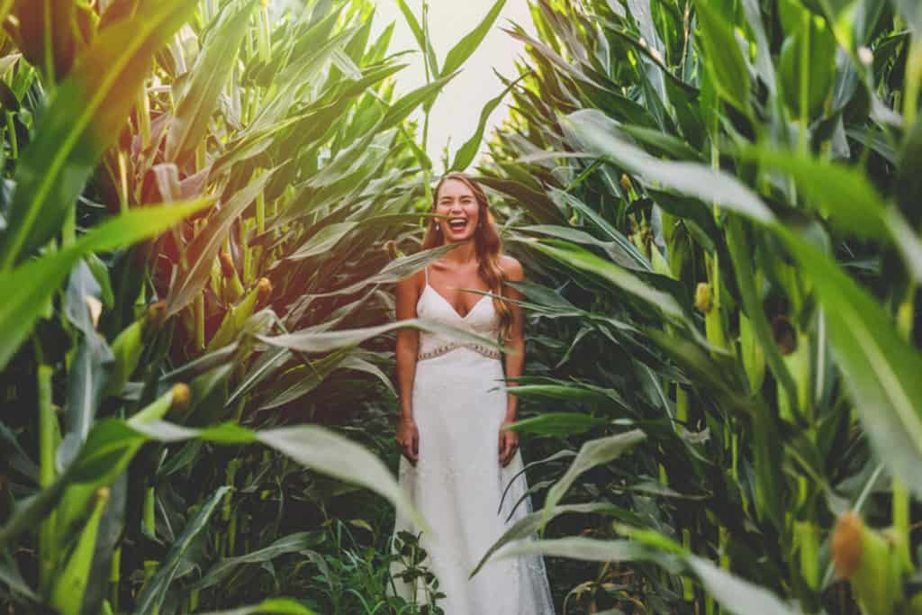 mega beautiful bride smiling and lighting up a green scene