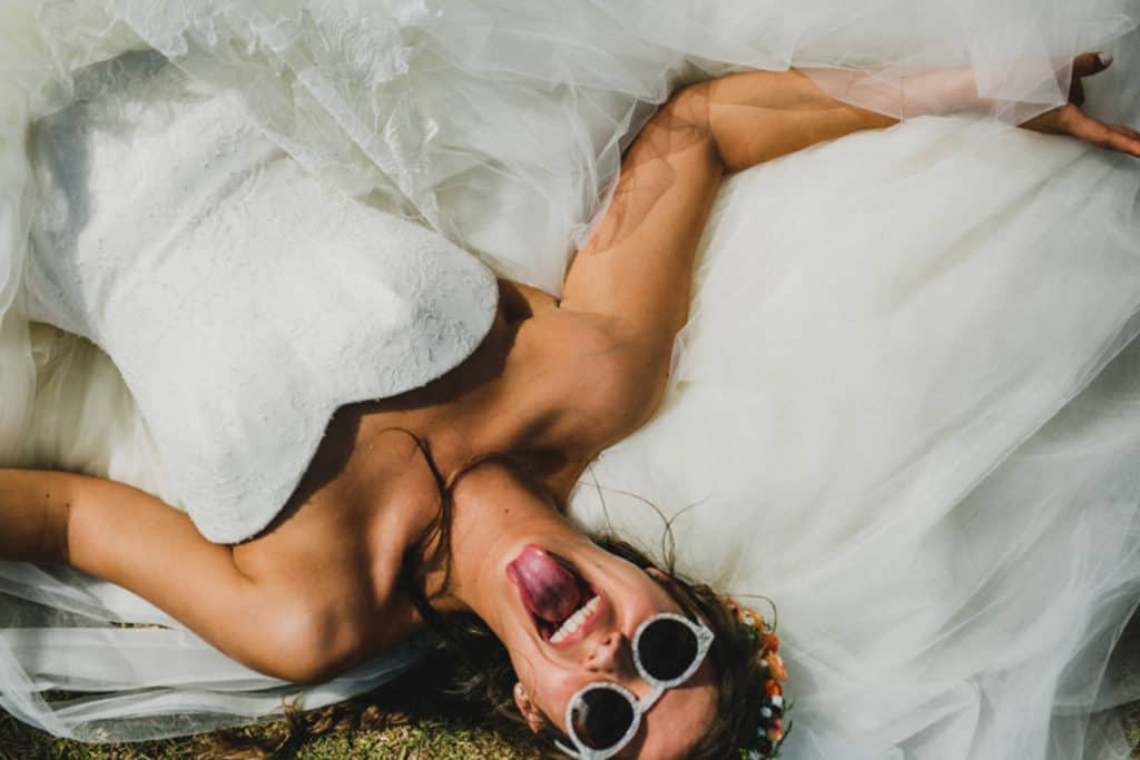 bride lying in the grass with sunglasses