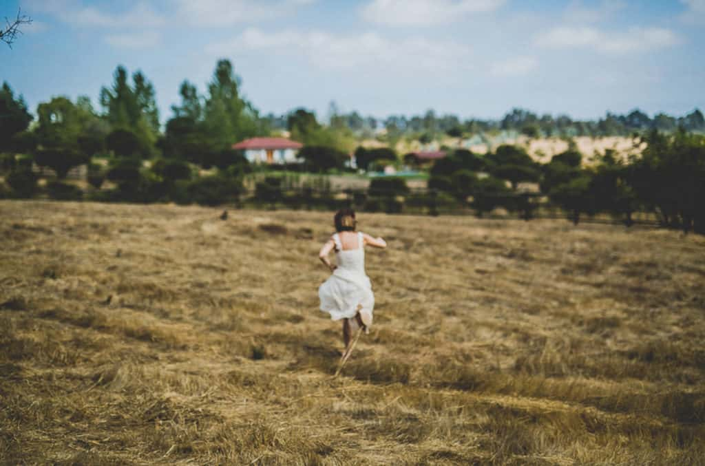 alternative bride running away in a wheat field