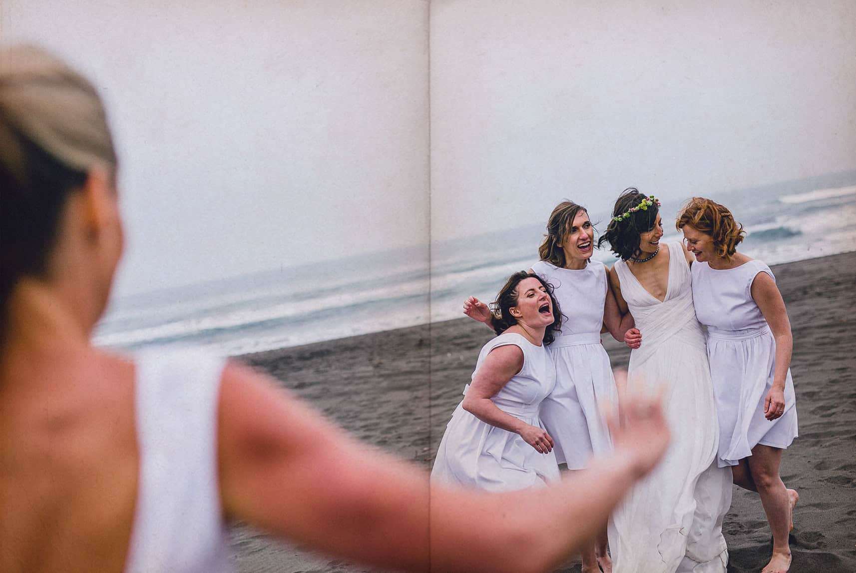 bride maids run to hug the bride at the beach