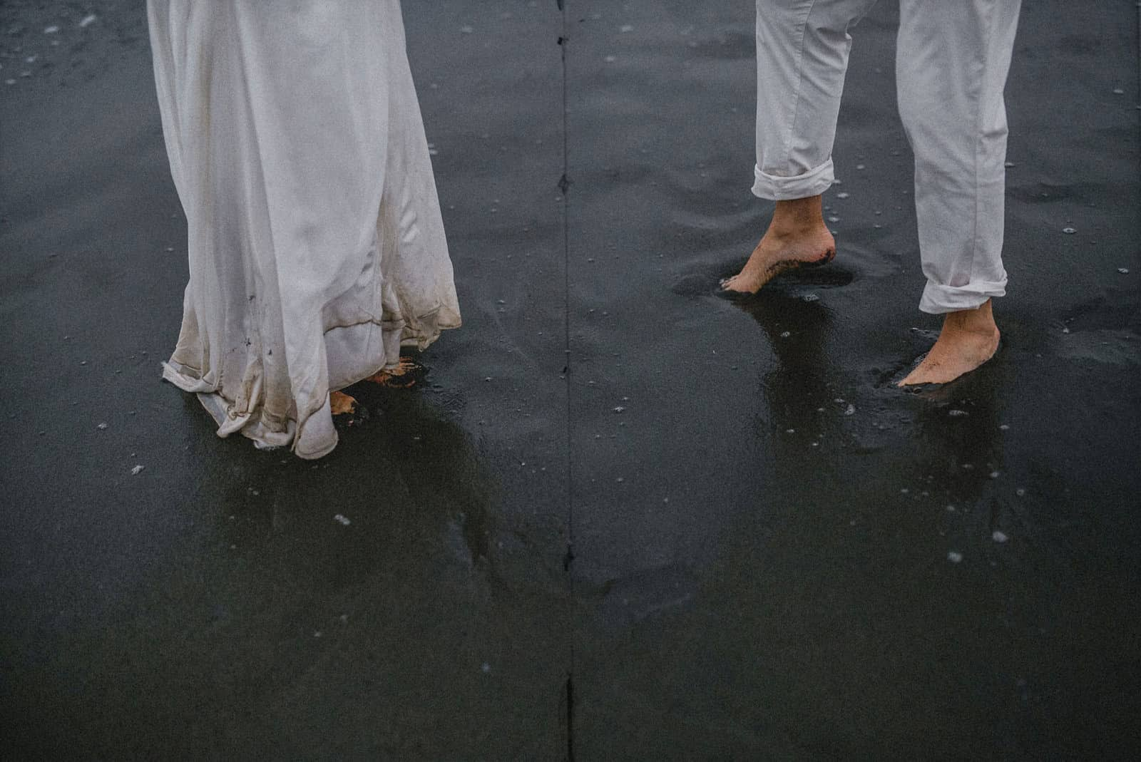 bride and groom wetting the feet and the dress in the water