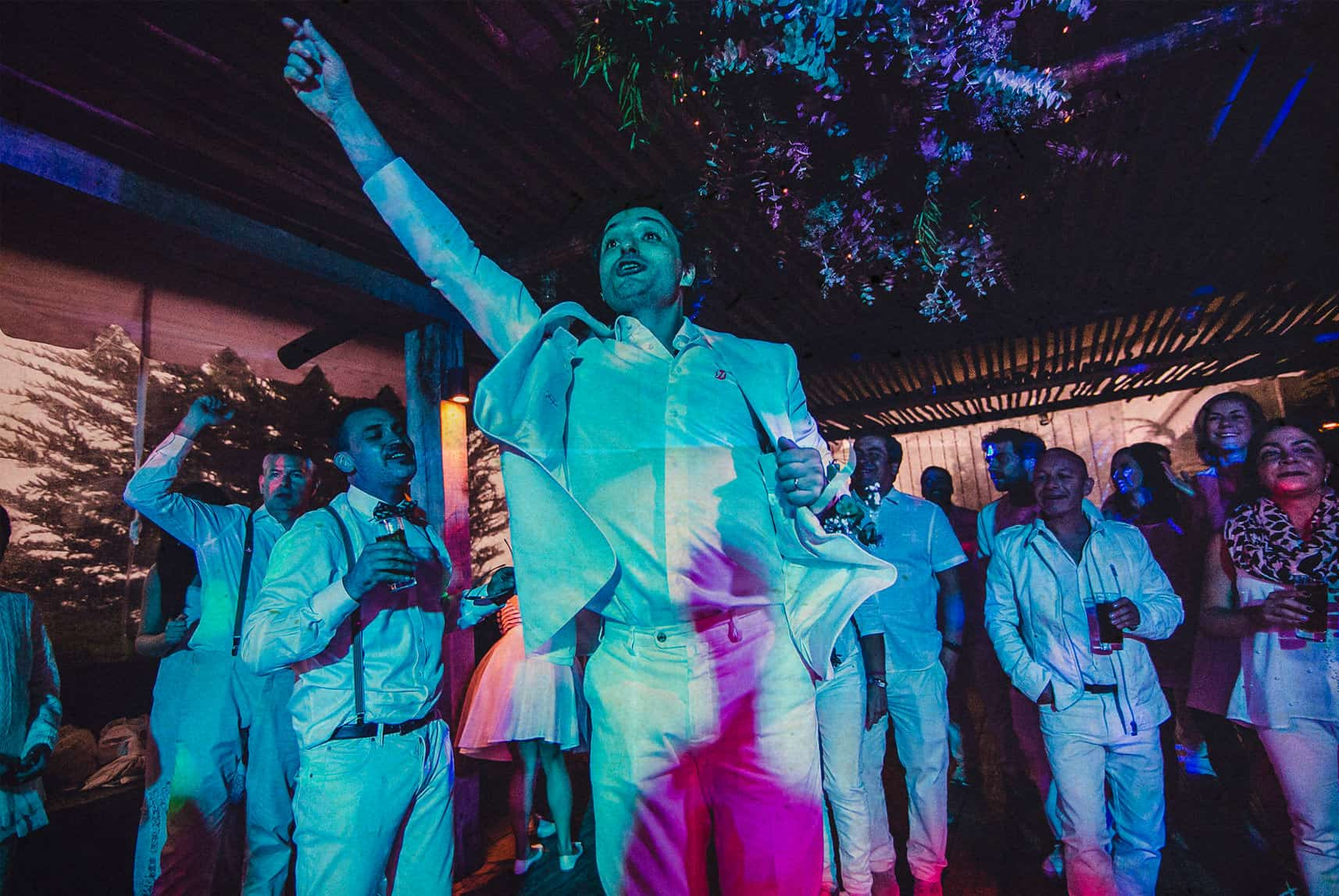 the groom jumping and screaming in the dance floor of the wedding