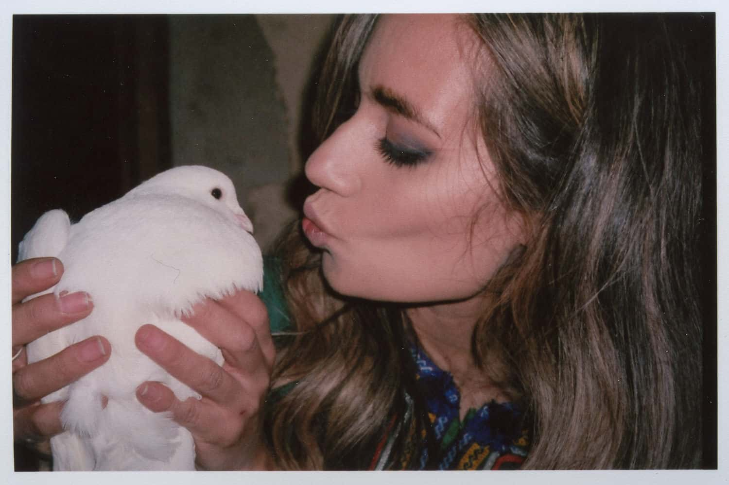 a girl kissing a pigeon