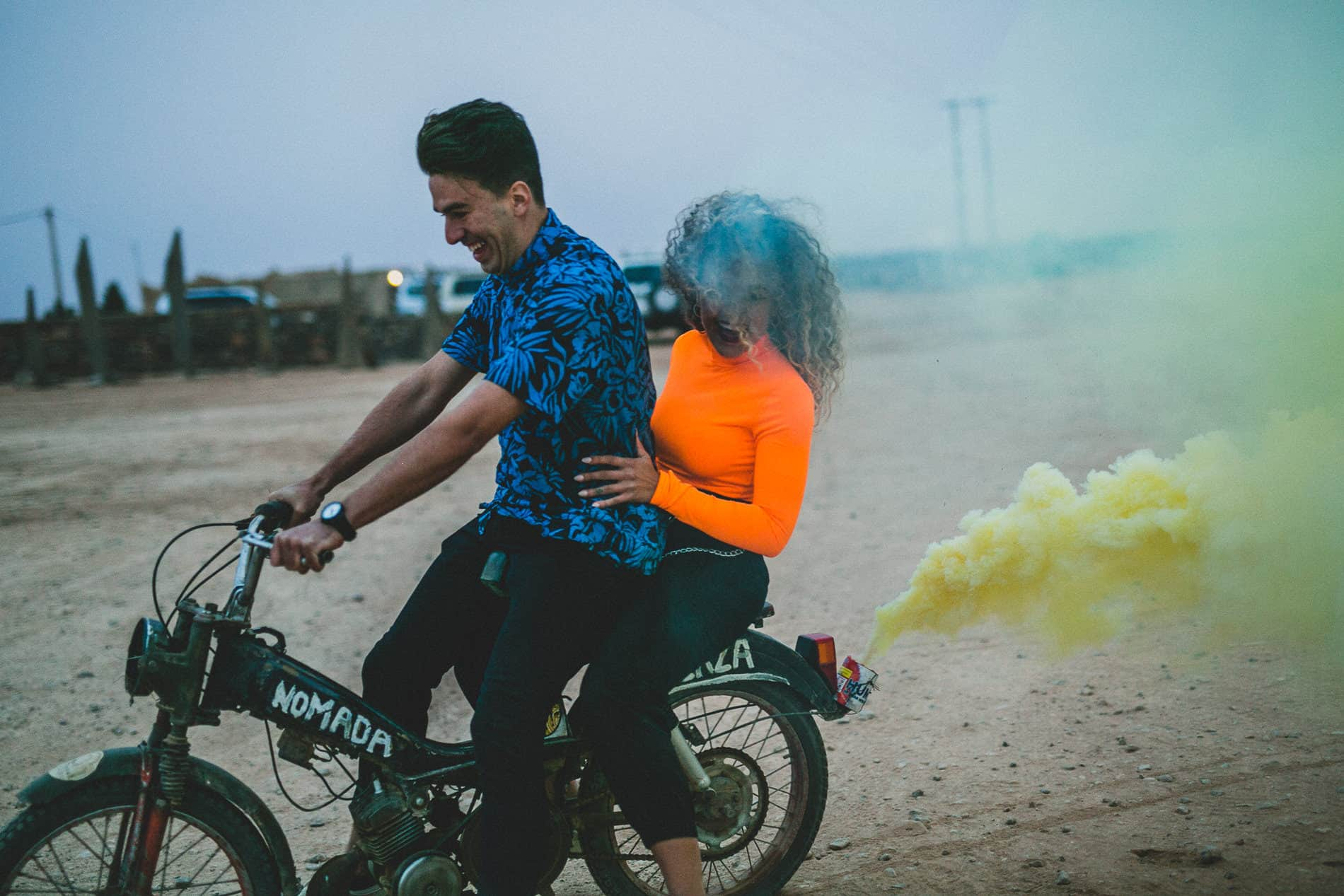 couple driving a motorcycle in the desert