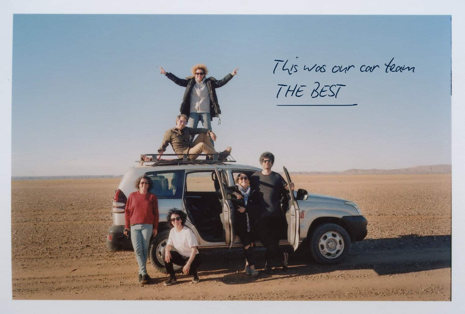 a group of photographers in a jeep in the middle of the desert
