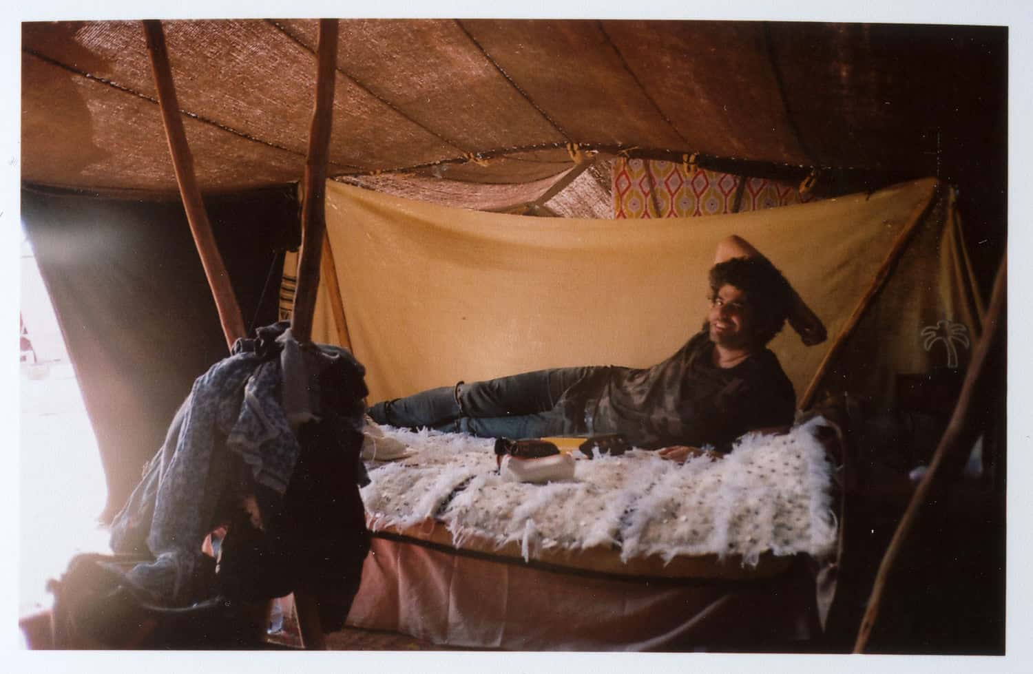 a man laying in a bed in a bereber tent