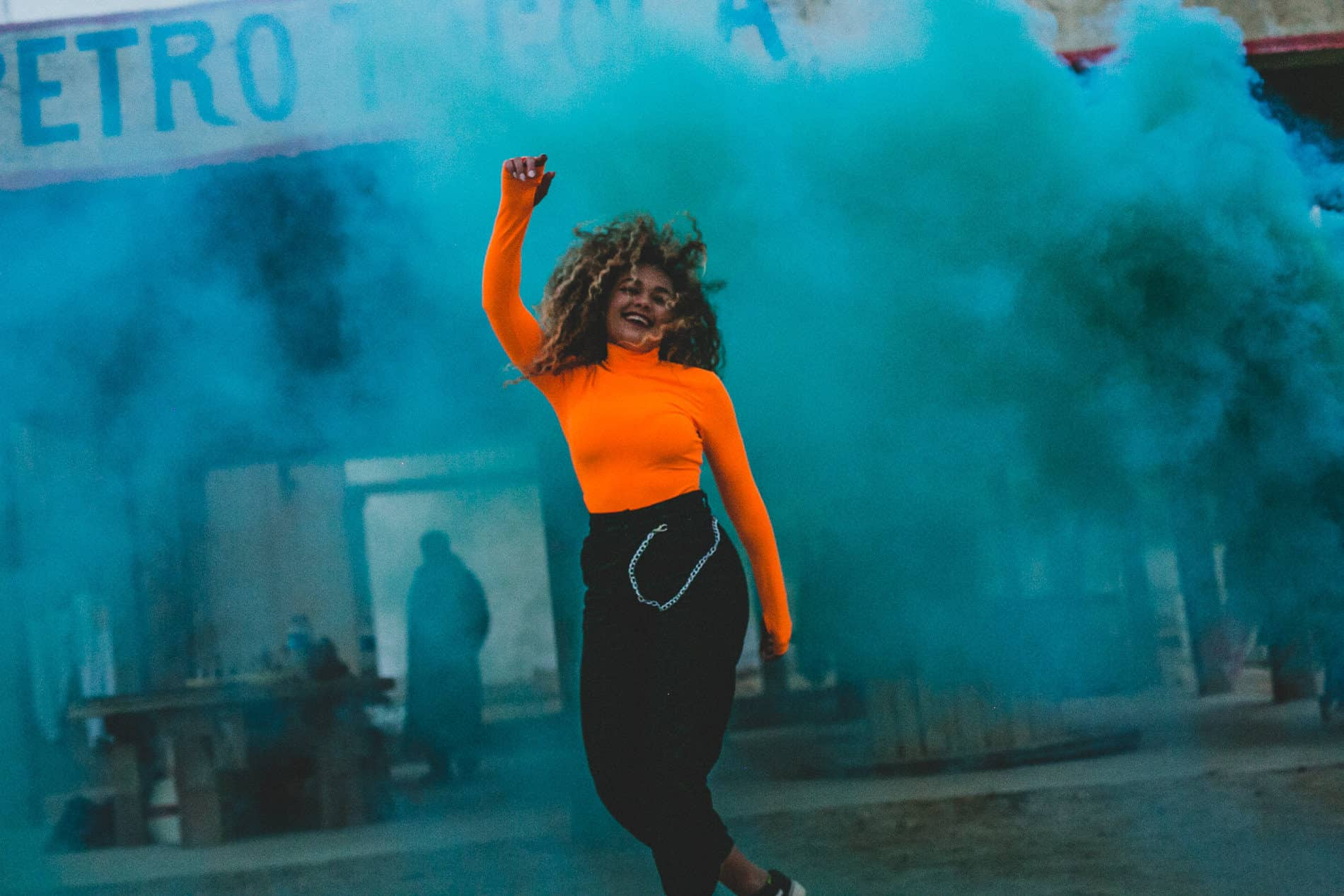 girl with an orange top dancing in blue fog