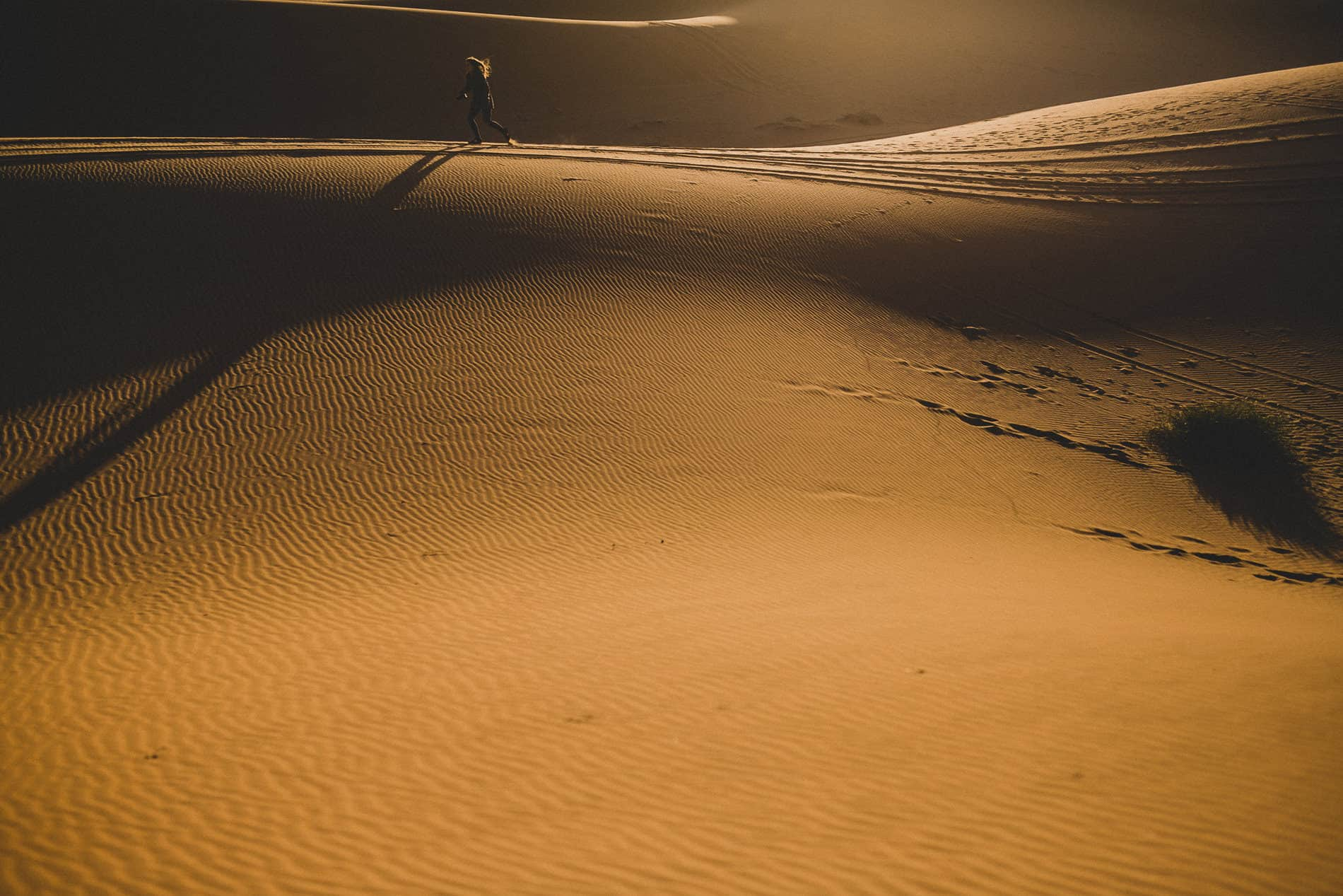 a girl is running in the dunes at sunset