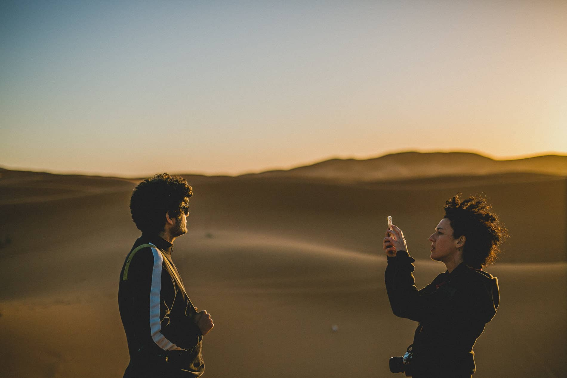 girl taking picture to a man in the sunset in between the dunes of merzouga desert