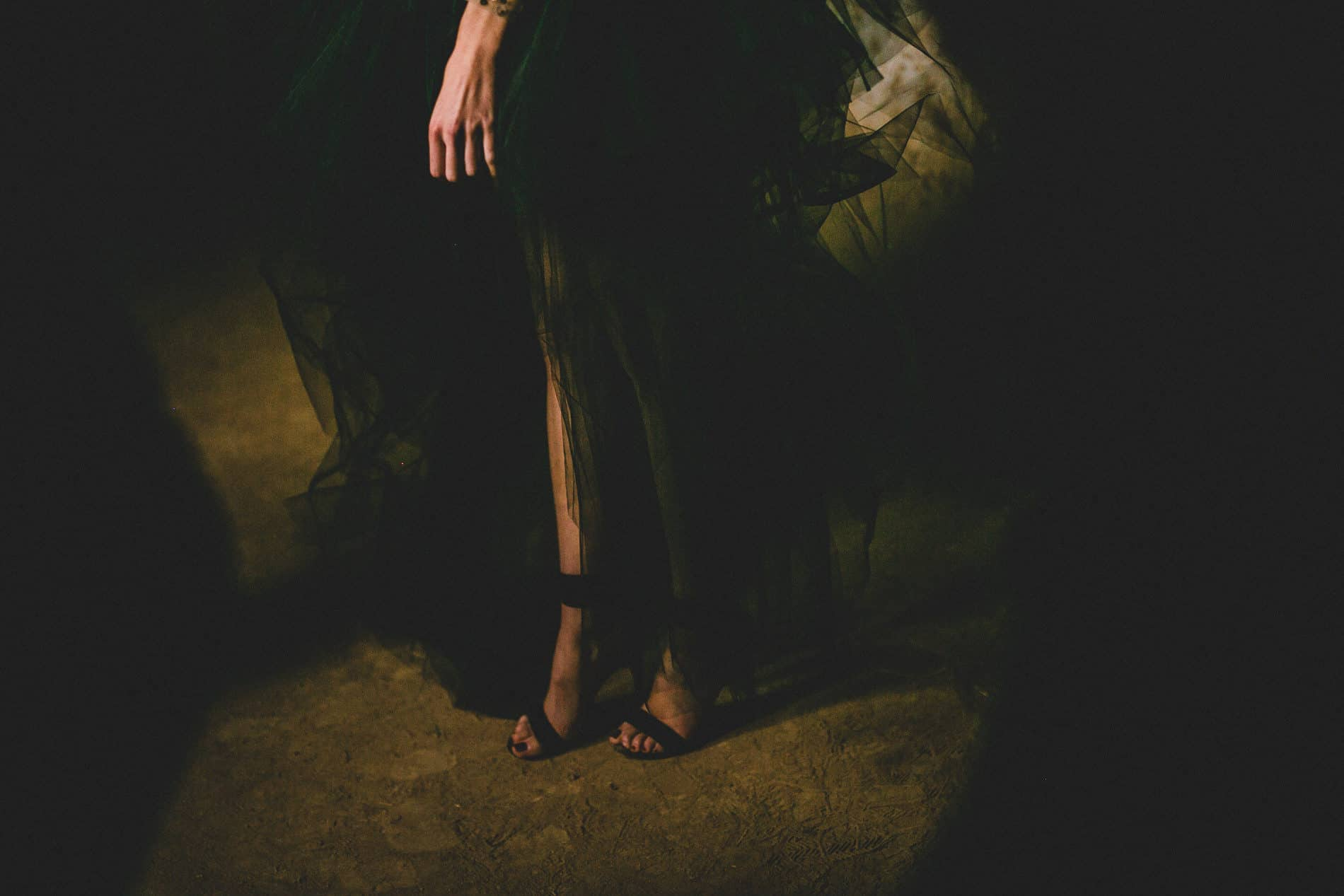 hand and foot of a bride dressed in a black dress