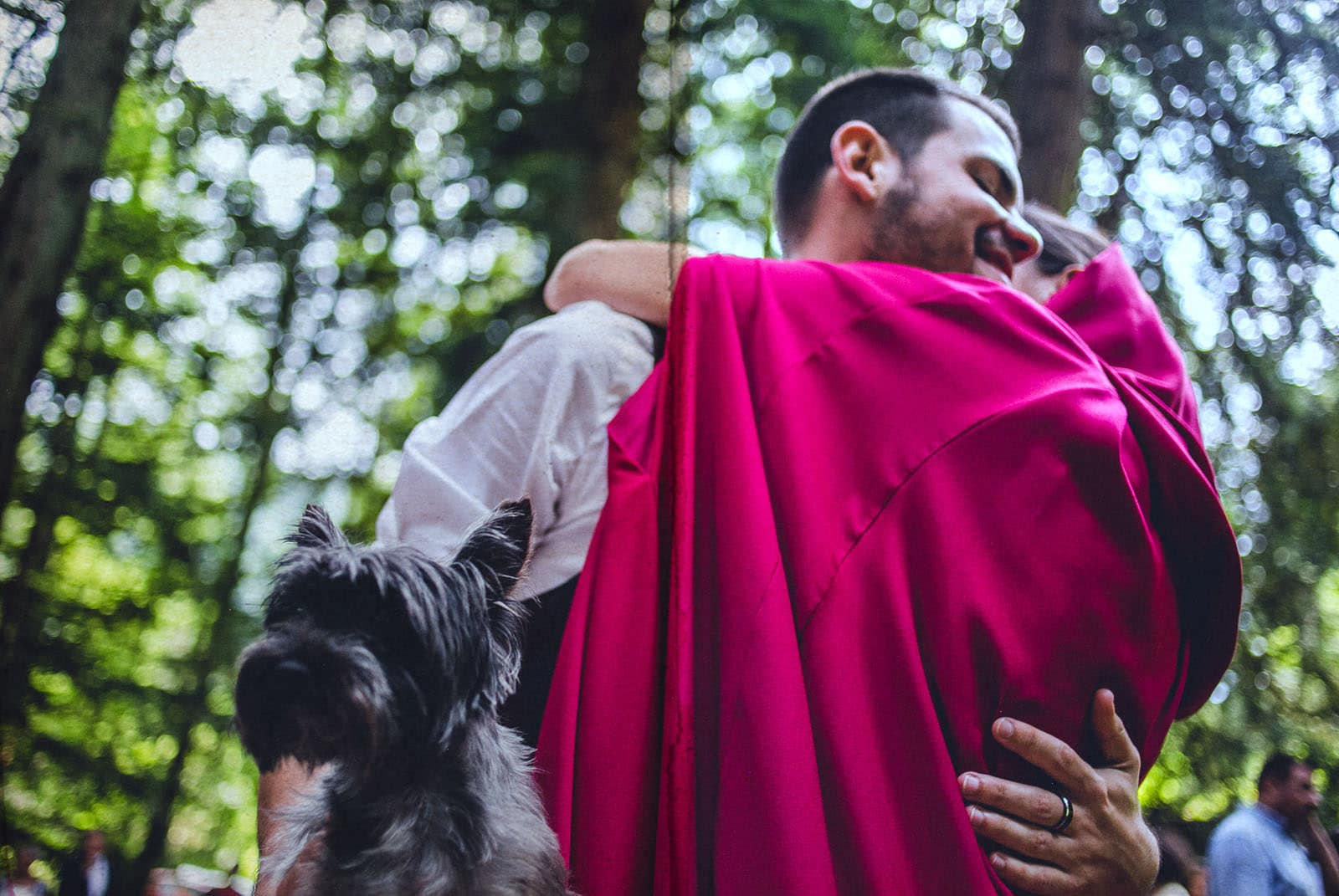 bride and groom hugging with their dog