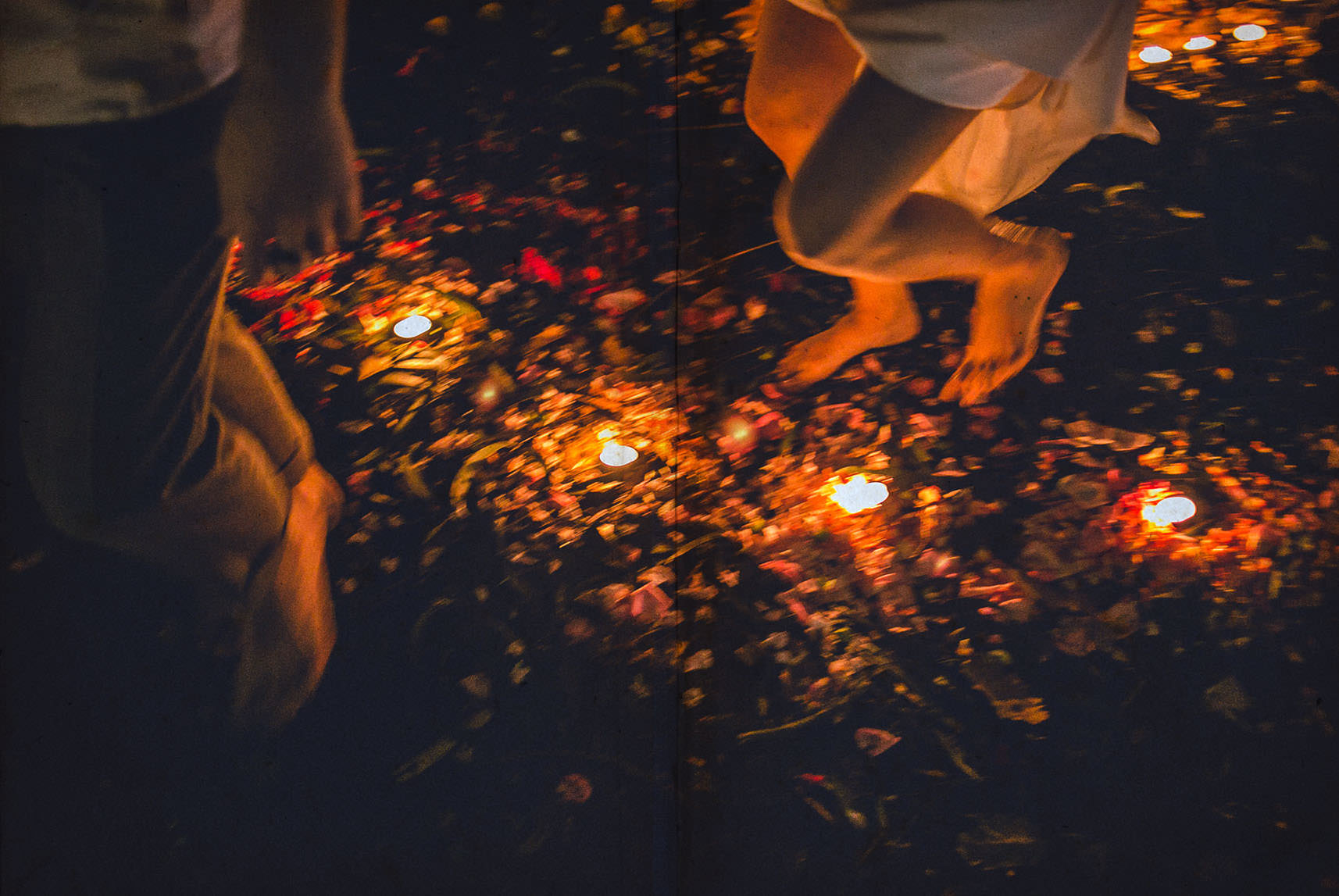 barefoots of bride and groom running between candles