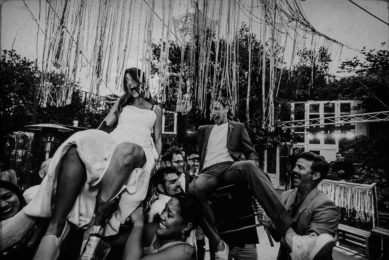 bride and groom lift it up in chairs in the middle of the party