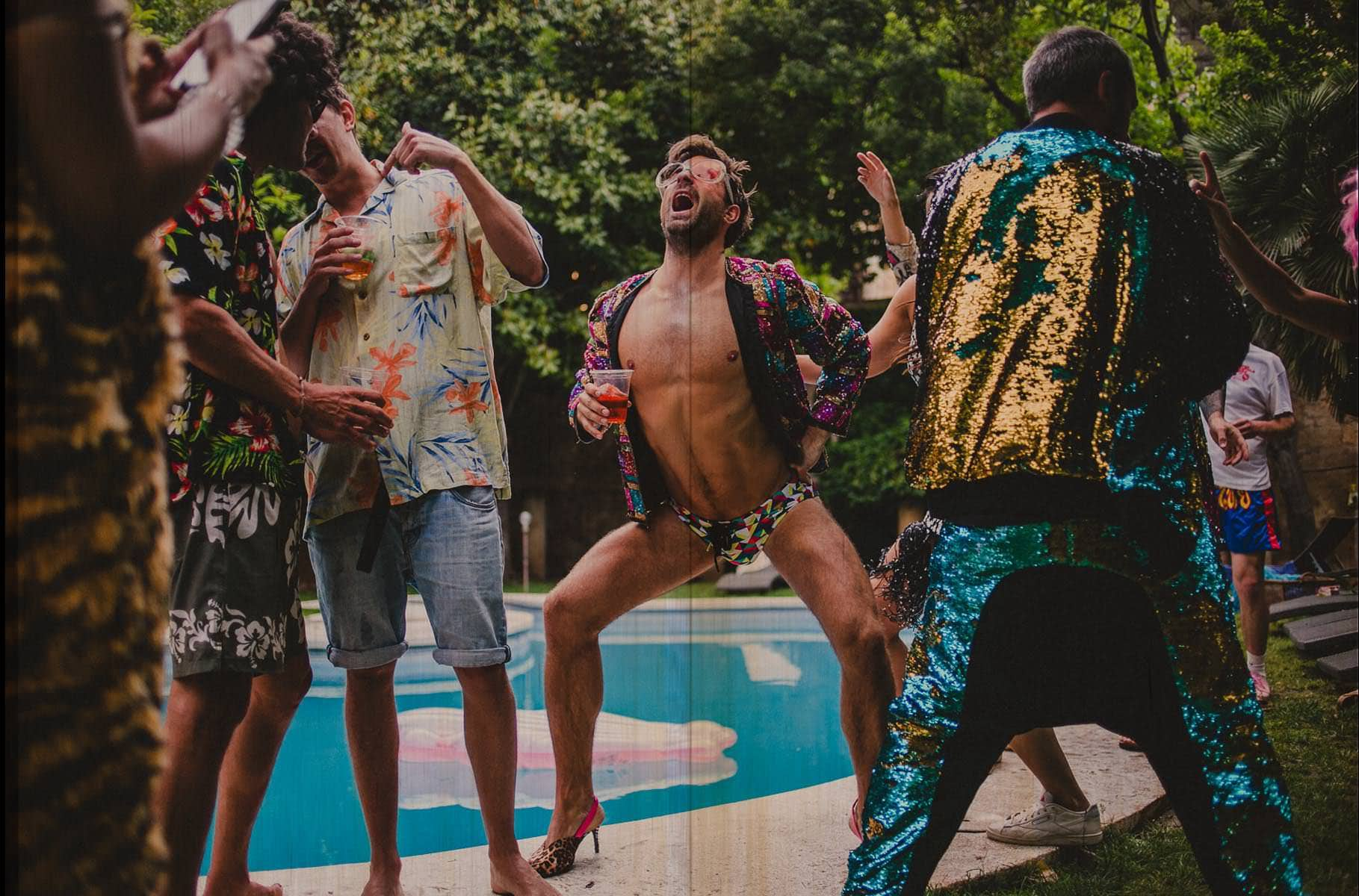 a guy dancing with heels in a pool party after a wedding