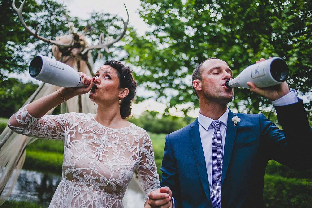 bride and groom drinking champagne from the bottle