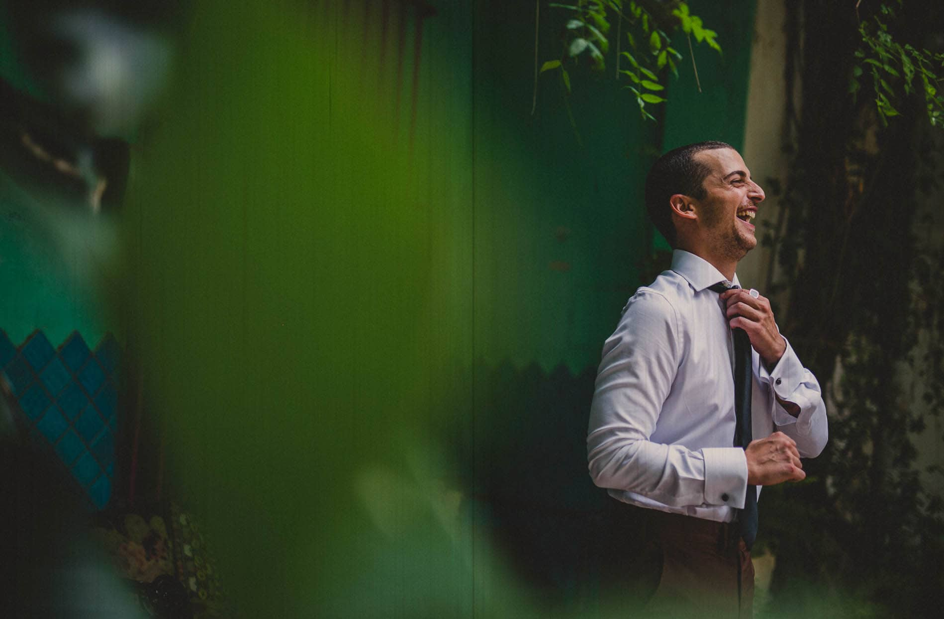 groom laughing while he`s getting ready