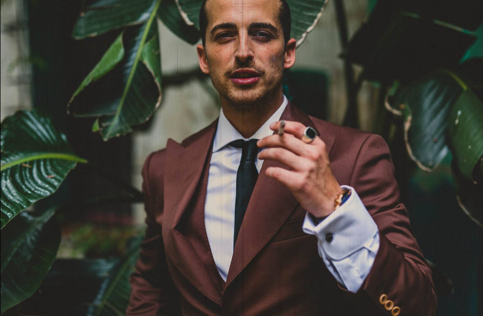 portrait of a groom in the middle of plants smoking