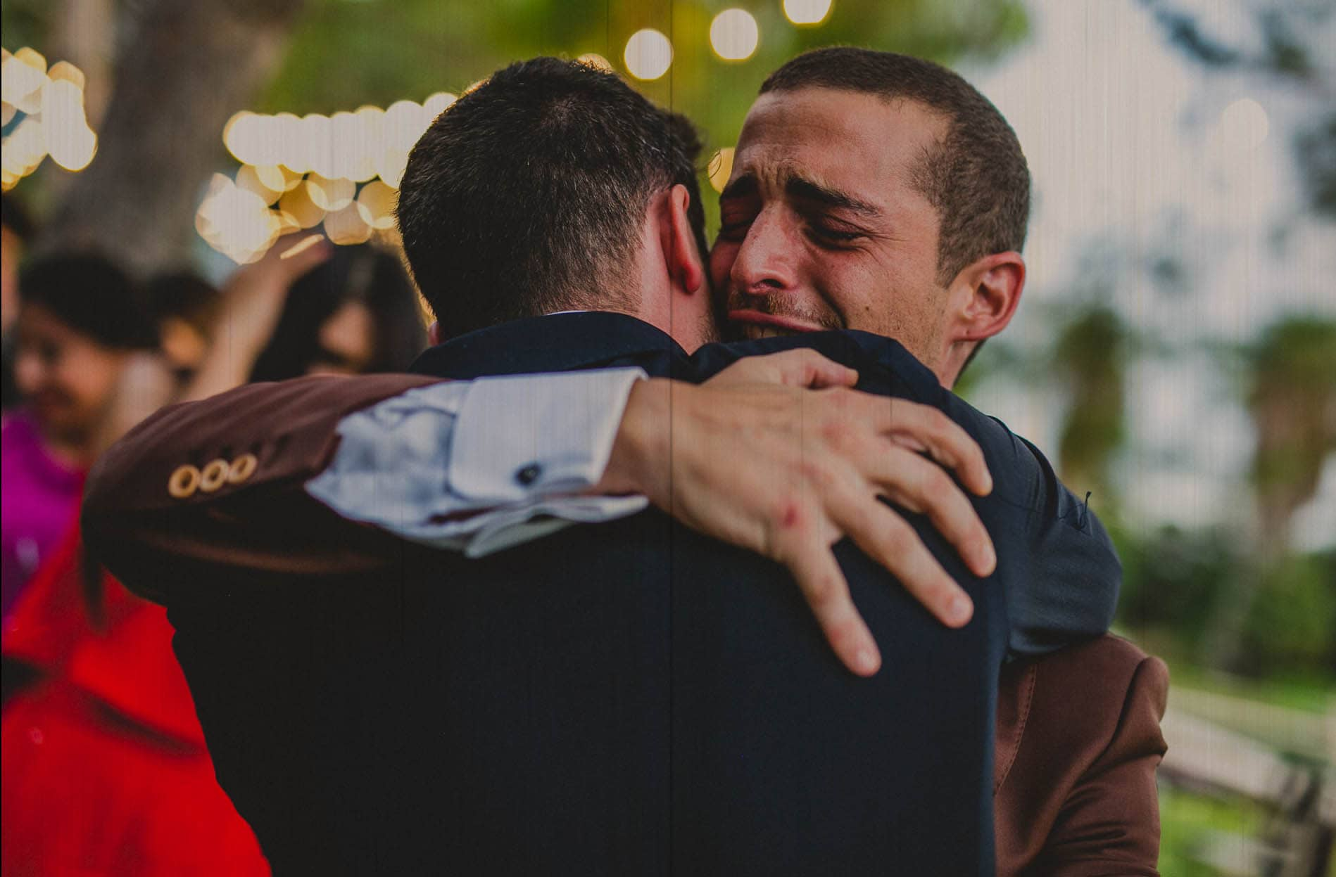 groom crying while he hugs his friend