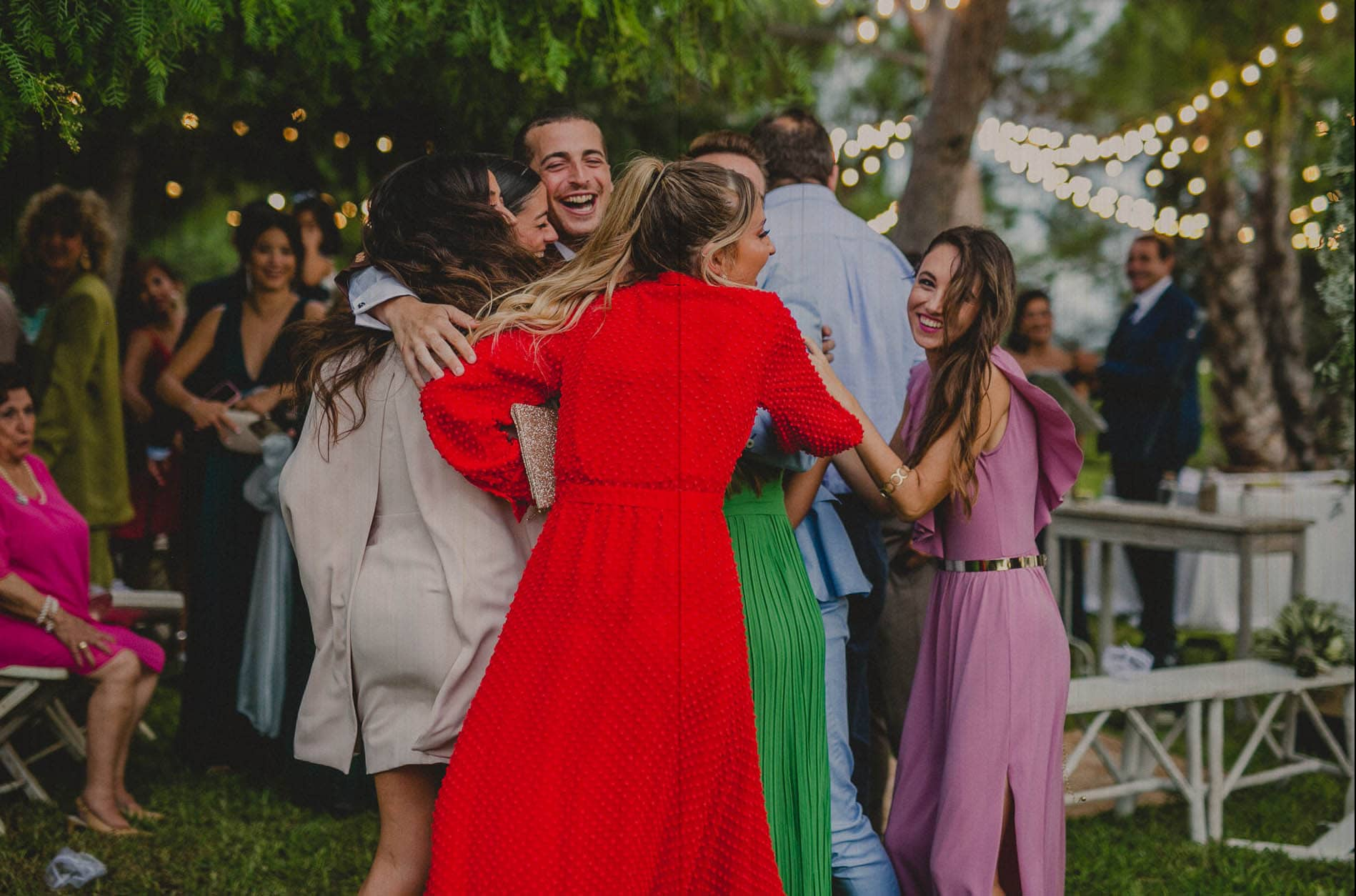 groom is hugged by friends